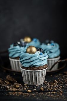 Kilka babeczek lub babeczek z niebieskim kremem w kształcie i jagodami na czarnym stole na ciemnym tle. copyspace w stylu rustykalnym.