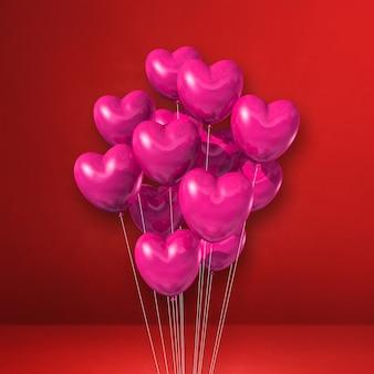 Kilka balonów kształt różowego serca na tle czerwonej ściany. renderowanie ilustracji 3d