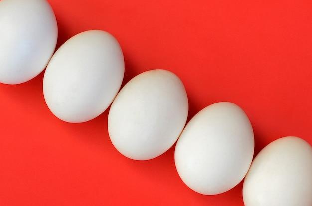 Kilka białych jaj na jasnym czerwonym tle