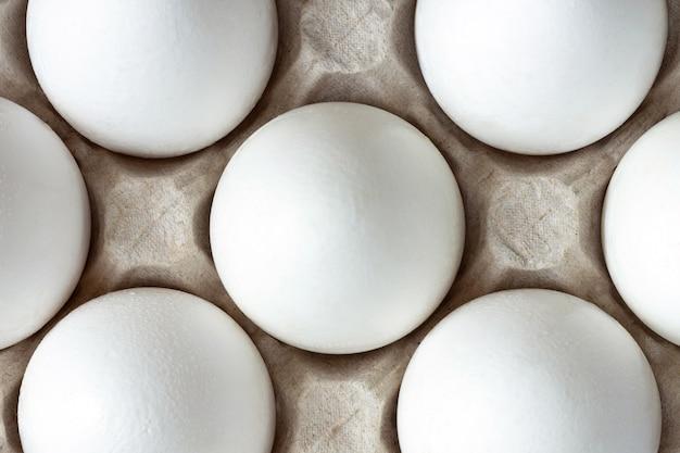 Kilka białych jajek umieszczonych w jasnobrązowym kartonie z widokiem z góry
