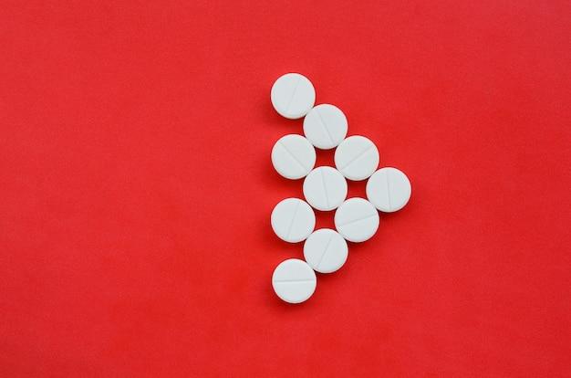 Kilka białych tabletek leży na jasnym czerwonym tle