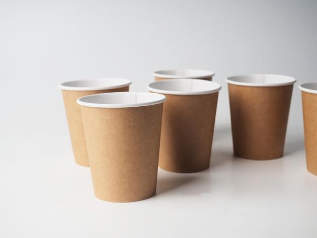 Kilka brązowych papierowych kubków jednorazowego użytku jest losowo umieszczonych na białym tle.