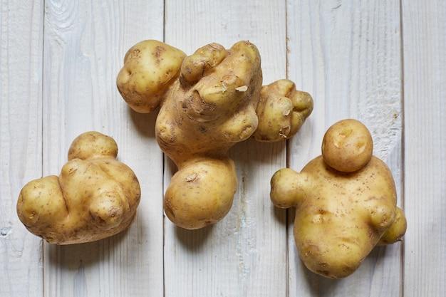 Kilka brzydkich ziemniaków na drewnianym stole. koncepcja odrzucenia przez sklep brzydkiego jedzenia. organiczne bez gmo