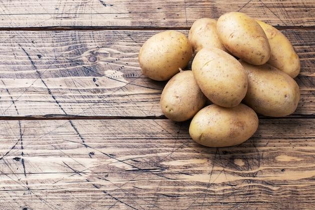 Kilka bulw surowych ziemniaków na drewnianym.