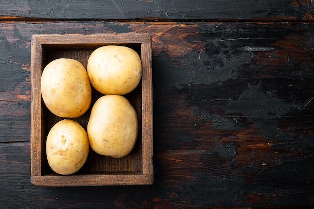 Kilka bulw surowych ziemniaków na starym drewnianym stole widok z góry z miejscem na tekst