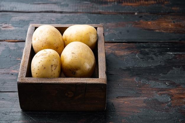 Kilka bulw surowych ziemniaków na starym drewnianym stole z miejscem na tekst