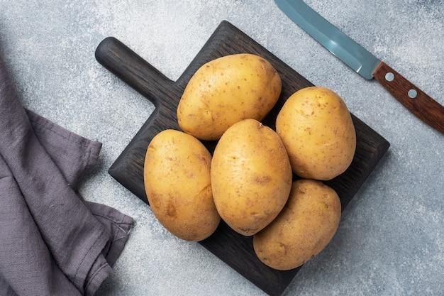 Kilka bulw surowych ziemniaków na szarym stole.