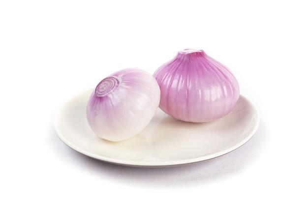 Kilka cebuli na białym talerzu na białym tle
