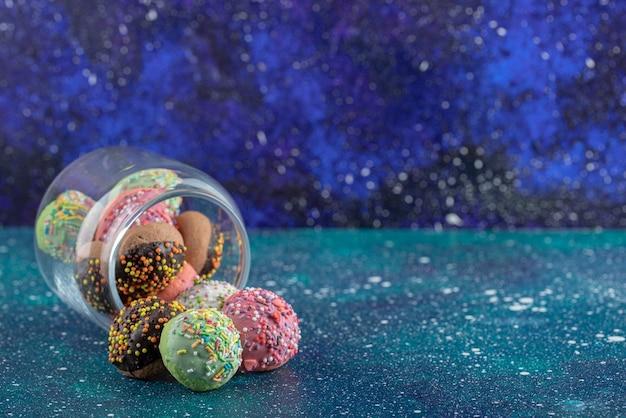 Kilka ciasteczek z cukierkami w szklanym słoju.