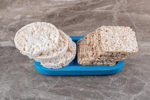 Kilka ciastek ryżowych na planszy, na marmurowej powierzchni