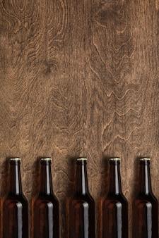 Kilka ciemnych piwnych butelek na drewnianym tle. widok z góry. copyspace.