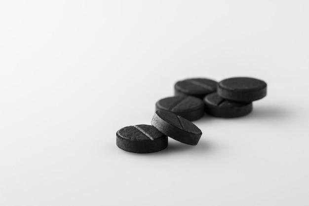 Kilka czarnych tabletek medycznych z węglem aktywowanym na białym tle. odosobniony