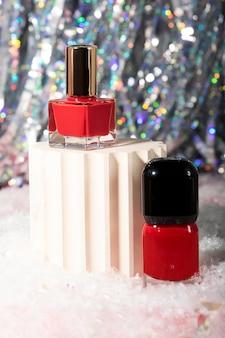 Kilka czerwonych butelek z lakierem do paznokci na podiumjasne tło i śnieg poniżejświąteczne kosmetyki