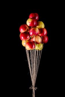 Kilka czerwonych i żółtych jabłek na rzemieślniczej sznurze jutowym, które latają jak balony. wspomnienie z dzieciństwa. pomysł koncepcyjny