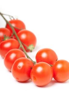Kilka czerwonych pomidorów czereśniowych na białym tle