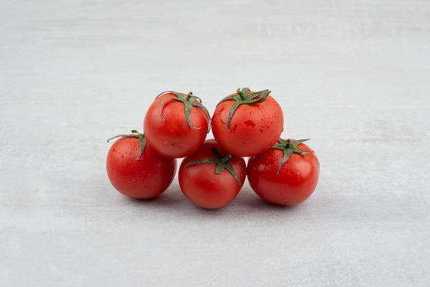 Kilka czerwonych pomidorów na białym tle.
