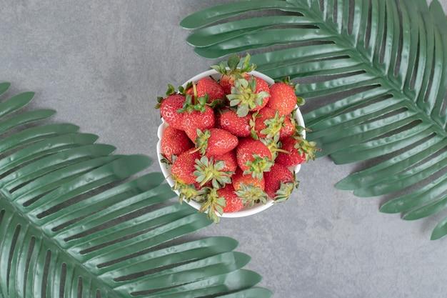 Kilka czerwonych truskawek w białej misce. zdjęcie wysokiej jakości