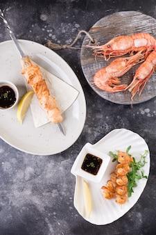 Kilka dań. kebaby z łososia i obranych krewetek z cytryną, sosem teriyaki i zielenią na białych talerzach oraz duże krewetki królewskie na desce.