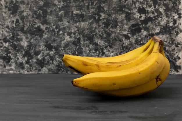 Kilka dojrzałych bananów na szarym tle vintage