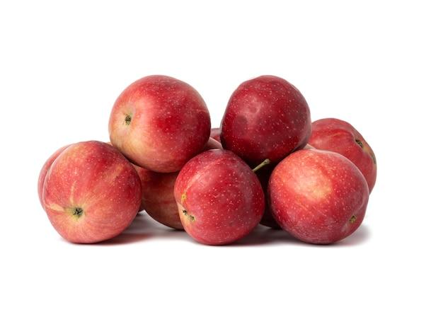 Kilka dojrzałych ciemnoczerwonych jabłek na białym tle