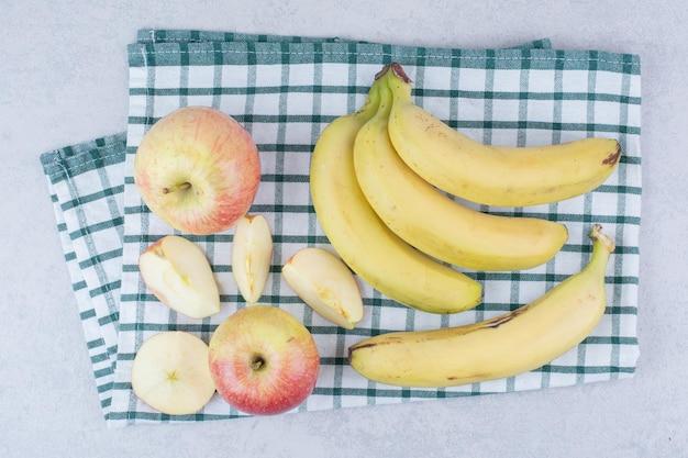 Kilka dojrzałych owoców bananów z pokrojonym jabłkiem na obrusie. zdjęcie wysokiej jakości