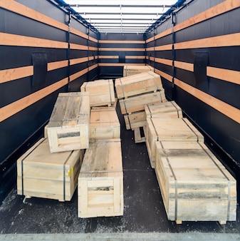 Kilka drewnianych skrzyń wewnątrz naczepy towarowej. pudła ułożone w nieuporządkowany stos. widok wnętrza pustej ciężarówki pół ciężarówki