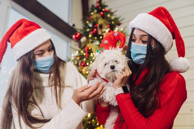 Kilka dziewcząt bawi się z małym psem w sylwestra w domu. boże narodzenie podczas koronawirusa, koncepcja