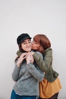 Kilka dziewczyn na białym tle patrzących w kamerę podczas przytulania