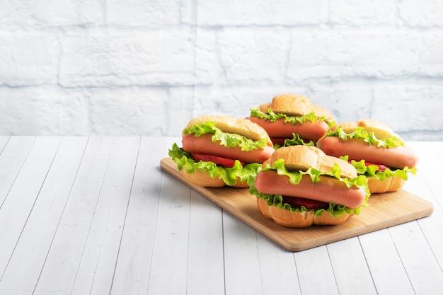 Kilka hot dogów na drewnianej desce. hot dog z sałatą, pomidorem i kiełbasą. skopiuj miejsce