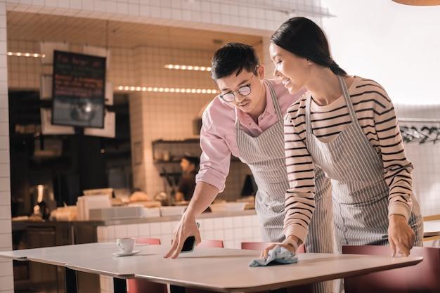 Kilka instrukcji. ciemnowłosy menadżer w okularach daje instrukcje kelnerce