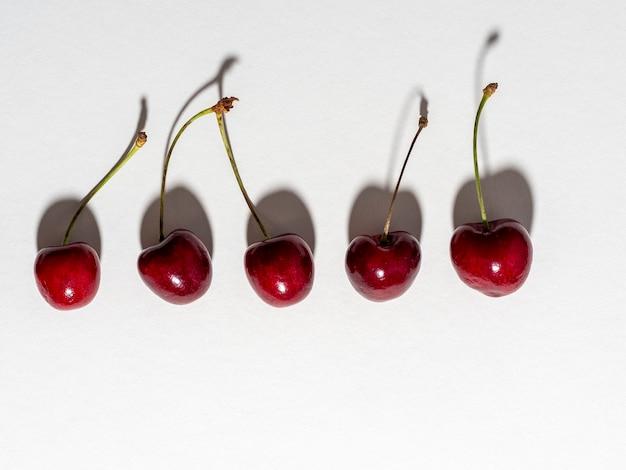 Kilka jagód wiśni jest ułożonych na białym tle i oświetlonych ostrym światłem