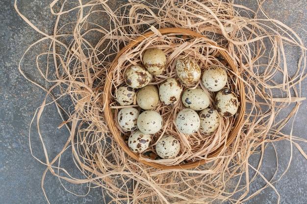 Kilka jaj przepiórczych w drewnianym gnieździe.