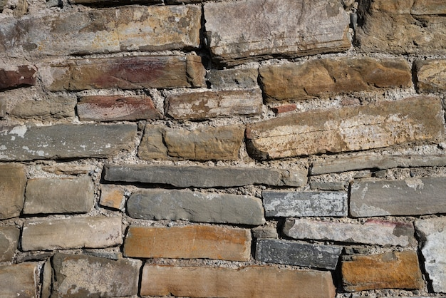 Kilka kamieni leży jeden na drugim w ścianie. kamienna tekstura