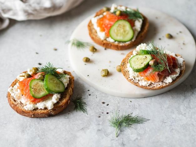 Kilka kanapek na chlebie żytnim z twarogiem, łososiem, świeżym ogórkiem i przyprawami.