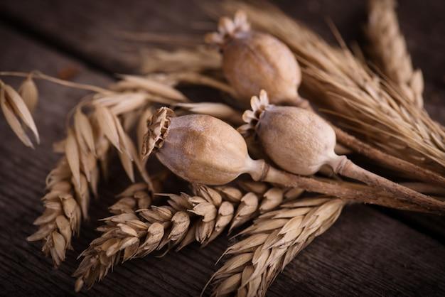 Kilka kłosów pszenicy i suchych maków na starym drewnianym stole.