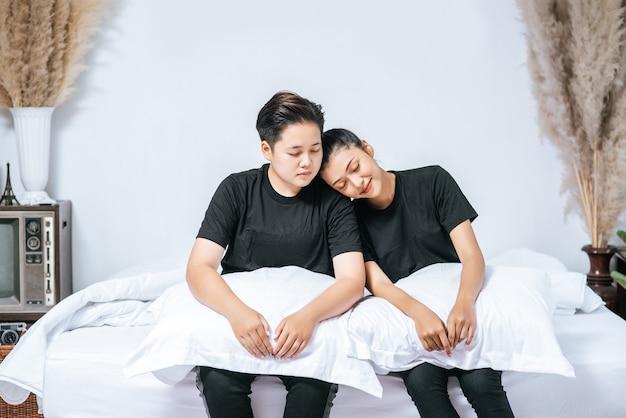 Kilka kobiet siedziało na łóżku z poduszkami podtrzymującymi nogi.