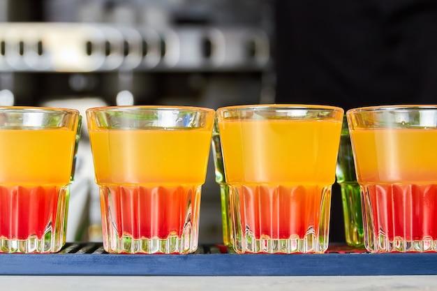 Kilka kolorowych kieliszków napojów alkoholowych na ladzie barowej