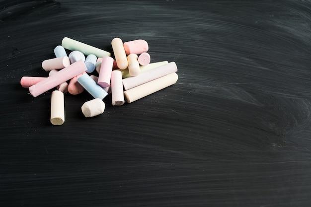Kilka kolorowych pastelowych kawałków kredy na tablicy