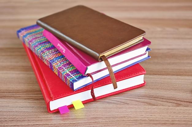 Kilka kolorowych zeszytów na drewnianym stole, widok z góry