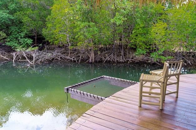 Kilka krzeseł na drewnianym tarasie z siatkowym siedziskiem, aby odpocząć nad zielonym morzem i lasem namorzynowym, zrelaksować się z naturą