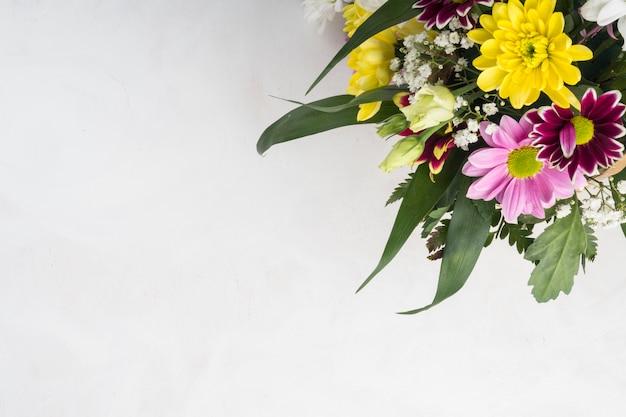 Kilka kwiatów letnich umieszczone na szarym biurku