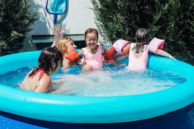Kilka lesbijek kąpie się w basenie z córkami w mufkach latem