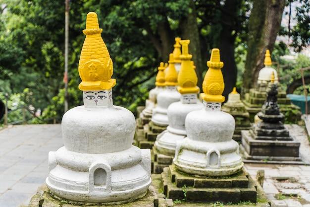 """Kilka małych białych stup z tradycyjnym obrazem """"oczy buddy"""" w rzędzie w świątyni swayambhunath, zwanej również świątynią małp. katmandu, podróż w koncepcji nepalu."""