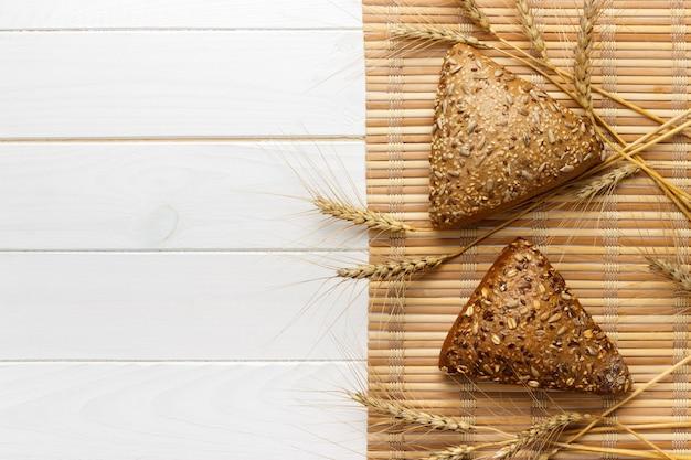 Kilka małych wieloziarnistych chlebów w kształcie trójkąta posypanych całymi ziarnami słonecznika