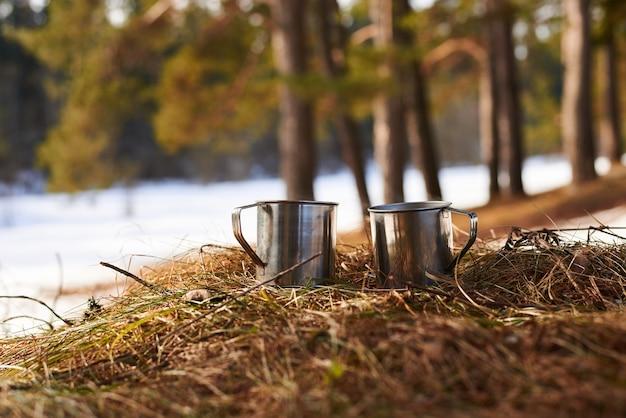 Kilka metalowych kubków z herbatą na zewnątrz na trawie wiosną w lesie