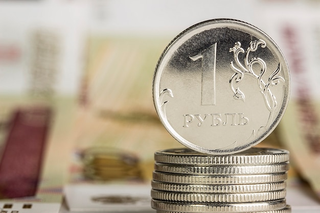 Kilka metalowych monet jednego rubla stojących na rosyjskich papierowych banknotach