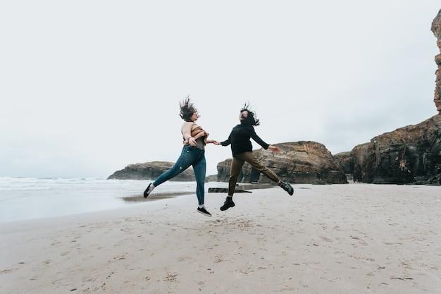 Kilka młodych kobiet skaczących na dzikiej plaży w słoneczny dzień