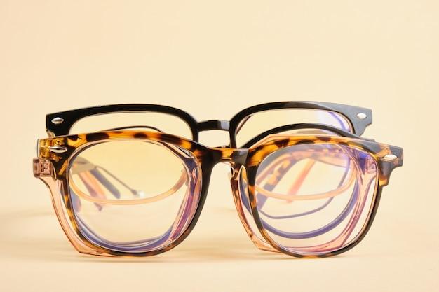 Kilka modnych modnych okularów korekcyjnych do korekcji wzroku na kolorowym tle, geometryczne tło z przestrzeni kopii na papierze pastelowym