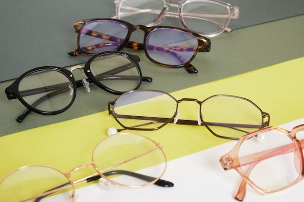 Kilka modnych stylowych okularów na geometrycznym zielonym tle kopiuje przestrzeń makiety