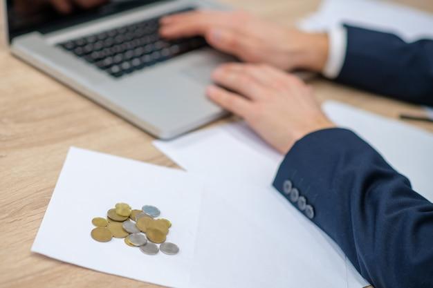 Kilka monet pieniędzy leżących na stole w pobliżu męskich rąk i laptopa